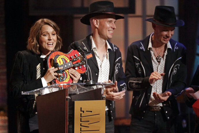 Brandi Carlile, left, accepts the Artist of the Year Award at the Americana Honors & Awards show Wednesday, Sept. 11, 2019, in Nashville, Tenn. (AP Photo/Wade Payne)