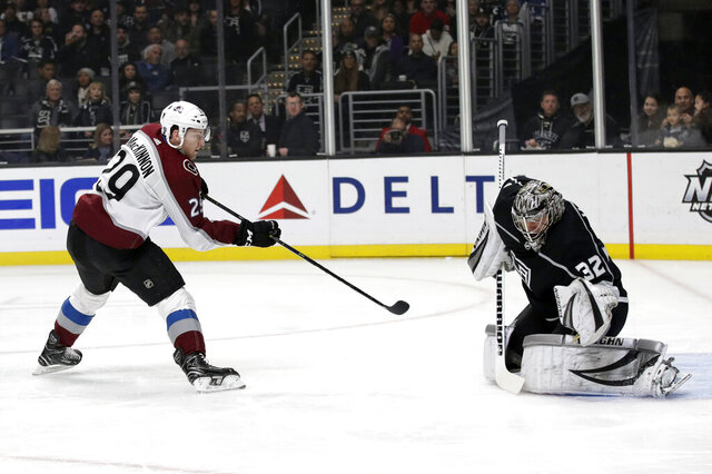 Los Angeles Kings goaltender Jonathan Quick, right, stops a shot from Colorado Avalanche's Nathan MacKinnon during the first period of an NHL hockey game Monday, March 9, 2020, in Los Angeles. (AP Photo/Marcio Jose Sanchez)