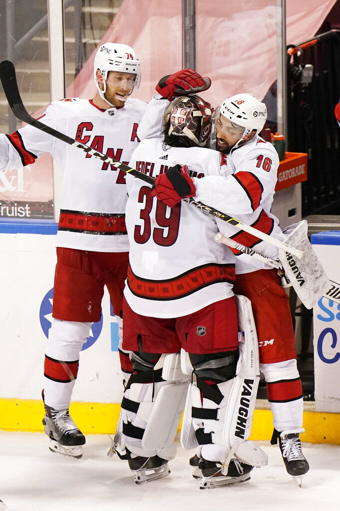 Carolina Hurricanes center Vincent Trocheck (16) and defenseman Jaccob Slavin (74) celebrate with goaltender Alex Nedeljkovic (39) after the Hurricanes defeated the Florida Panthers 3-2 in an overtime period of an NHL hockey game, Monday, March 1, 2021, in Sunrise, Fla. (AP Photo/Wilfredo Lee)