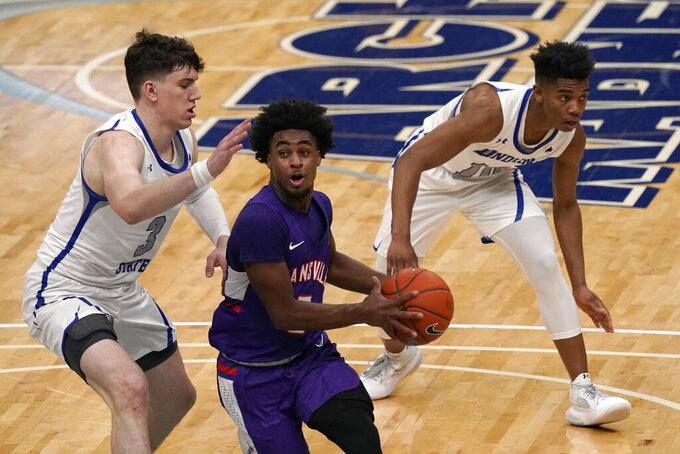 Evansville's Shamar Givance, center, heads to the basket as Indiana State's Jake LaRavia (3) and Julian Larry, right, defend during the first half of an NCAA college basketball game in the quarterfinal round of the Missouri Valley Conference men's tournament Friday, March 5, 2021, in St. Louis. (AP Photo/Jeff Roberson)