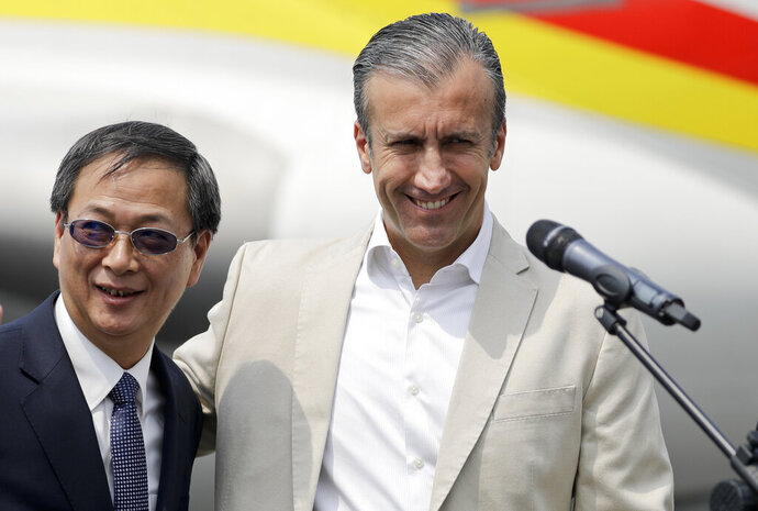 Chinese Ambassador Li Baorong, left, and Tareck El Aissami, Venezuela's minister of industry and national production, arrive to talk to reporters at the Simon Bolivar International Airport in Maiquetia, near Caracas, Venezuela, Friday, March 29, 2019. Aid was unloaded from a Chinese plane in what Venezuelan officials said would be the first delivery of many from China, an ally of the government of President Nicolas Maduro. (AP Photo/Natacha Pisarenko)