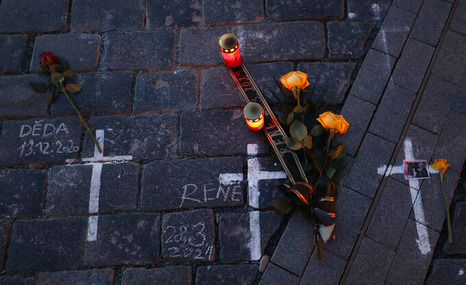 Candles and flowers are placed to pay respect to victims of the COVID-19 pandemic at a spontaneous memorial place set at the Old Town Square in Prague, Czech Republic, Monday, March 29, 2021. The coronavirus pandemic is unleashing enormous suffering as infection rates rise across central Europe even as the Czech Republic and Slovakia, recently among the worst-hit areas in the world, are finally seeing some improvements following tight lockdowns. (AP Photo/Petr David Josek)