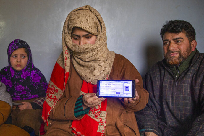 """Zarqa Mushtaq, center, shows on a mobile phone the 11th grade examination slip of her 16 -year old brother Athar Mushtaq, as her father Mushtaq Ahmad Wani, looks on while talking to the Associated Press in Bellow, south of Srinagar, Indian controlled Kashmir, Tuesday, Jan. 5, 2021. On the last week of 2020, Indian government forces killed Athar and two other young men during a controversial gunfight on the outskirts of the Indian-controlled Kashmir's main city. Police did not call them anti-India militants but """"hardcore associates of terrorists."""