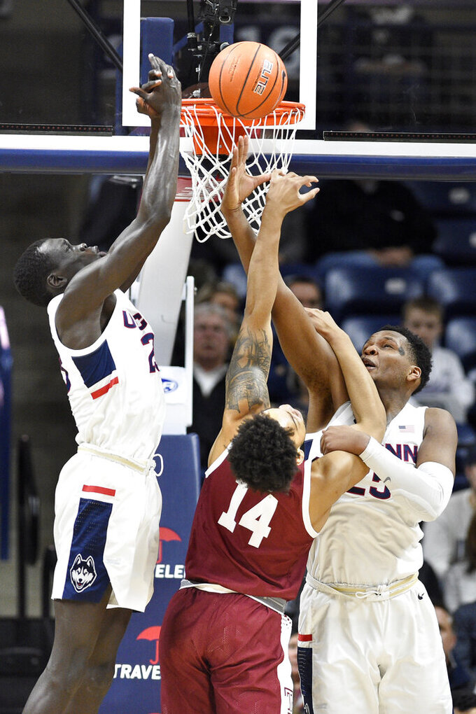 Connecticut's Akok Akok, left, and Connecticut's Josh Carlton, right, defend a shot attempt by Temple's Nate Pierre-Louis, center, in the first half of an NCAA college basketball game, Wednesday, Jan. 29, 2020, in Storrs, Conn. (AP Photo/Jessica Hill)