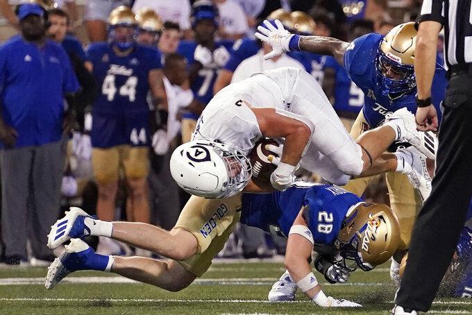 UC Davis' Lan Larison (3) tumbles over Tulsa safety Jett Hendrix (28) during the second half of an NCAA college football game Thursday, Sept. 2, 2021, in Tulsa, Okla. (AP Photo/Sue Ogrocki)