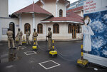 Policemen stand guard next to markings made to ensure physical distancing outside the Kochi Special Economic Zone during a nation wide strike by various trade unions in Kochi, Kerala state, India, Thursday, Nov. 26, 2020.  India has more than 9 million cases of coronavirus, second behind the United States. (AP Photo/R S Iyer)