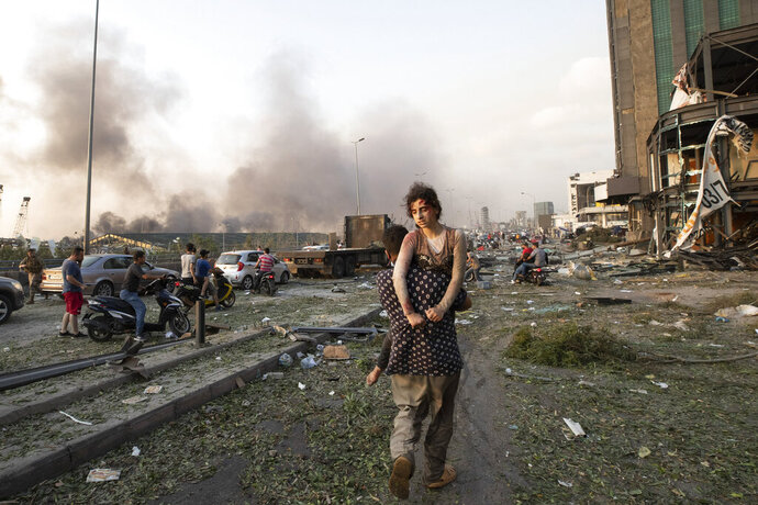 People evacuate wounded after of a massive explosion in Beirut, Lebanon, Tuesday, Aug. 4, 2020. (AP Photo/Hassan Ammar)