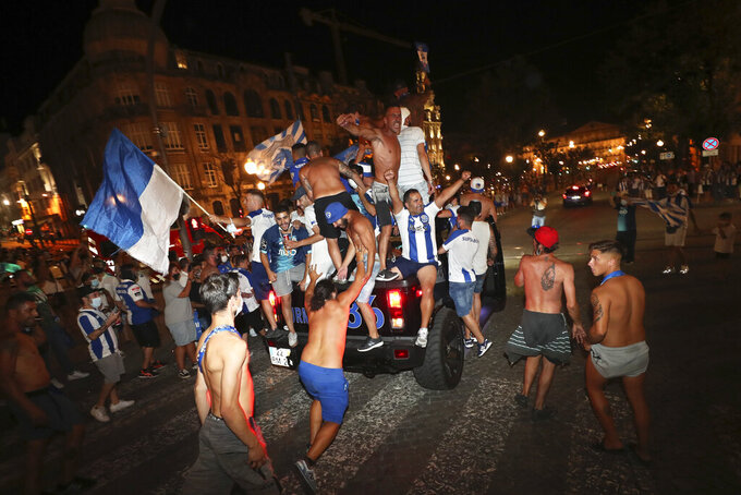 FILE - In this July 16, 2020 file photo, FC Porto fans ride on top of a vehicle while celebrating in downtown Porto, Portugal, after their team beat Sporting CP 2-0 to win the championship. Portugal is taking center stage for soccer during the next two weeks — a country where rivalries between clubs go well beyond the field of play. The decisive stages of the Champions League will begin on Wednesday Aug. 12, 2020, in the southern European nation where back-and-forth accusations and legal actions involving the country's top teams are routine. (AP Photo/Miguel Angelo Pereira, File)