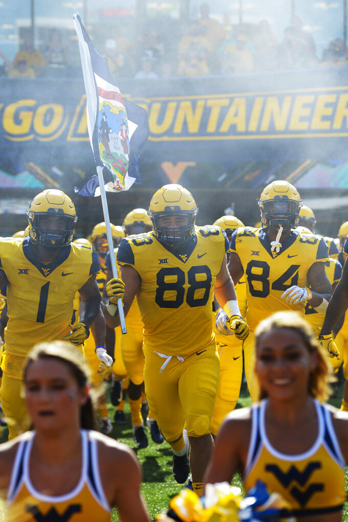 West Virginia Mountaineers tight end Trevon Wesco (88) carries the flag of West Virginia as the Mountaineers take to the field to play against the University of Kansas Jayhawks in Morgantown, W. Va., Saturday Oct. 6, 2018. (AP Photo/Craig Hudson)