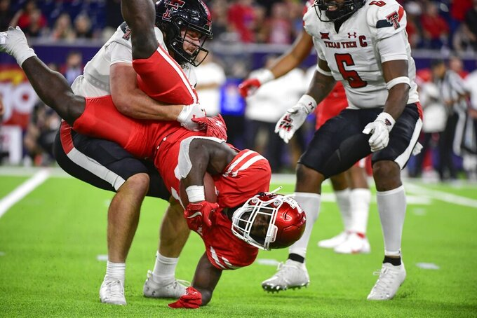 Texas Tech linebacker Colin Schooler (17) tackles Houston wide receiver KeSean Carter (20) during the second half of an NCAA college football game Saturday, Sept. 4, 2021, in Houston. (AP Photo/Justin Rex)