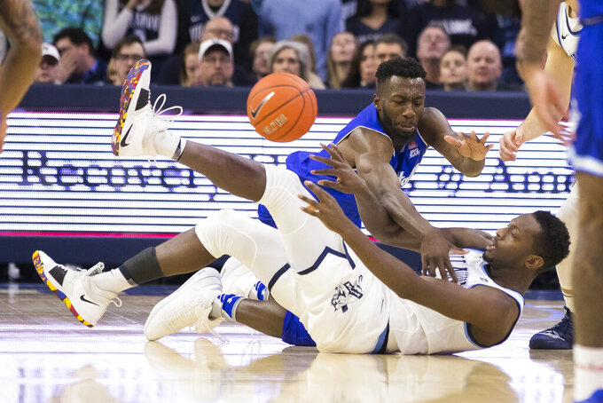 Villanova's Dhamir Cosby-Roundtree, right, passes the ball away before Seton Hall's Michael Nzei, left, can get to him during the first half of an NCAA college basketball game, Sunday, Jan. 27, 2019, in Philadelphia. (AP Photo/Chris Szagola)