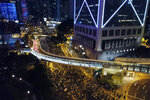 In this Sunday, Dec. 8, 2019, photo, pro-democracy protesters march into the night in central Hong Kong. Hundreds of thousands thronged Hong Kong streets Sunday, in a mass show of support for a protest movement that shows no signs of flagging as it enters a seventh month. (AP Photo/Dake Kang)