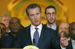 FILE - In this March 13, 2019, file photo, flanked by lawmakers, Gov. Gavin Newsom discusses his decision to place a moratorium on the death penalty during a news conference at the Capitol in Sacramento, Calif. California's Supreme Court has refused to block death penalty cases from continuing during Gov. Gavin Newsom's moratorium on executions. The justices on Wednesday, Sept. 11, 2019, rejected defense attorneys' arguments that jurors can't realistically gauge the seriousness of imposing a death sentence if they think it's never actually going to be carried out. Newsom halted executions in March for as long as he remains governor. (AP Photo/Rich Pedroncelli, File)