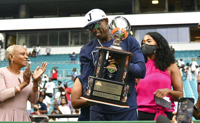 Jackson State head football coach Deion Sanders, center, holds the Orange Blossom Classic trophy after winning an NCAA college football game over Florida A&M, Sunday, Sept. 5, 2021, in Miami Gardens, Fla. (AP Photo/Jim Rassol)