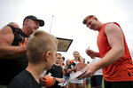 Cincinnati Bengals quarterback Andy Dalton (14) signs autographs for fans during NFL football practice in Cincinnati, Tuesday, Aug. 13, 2019.  (Kareem Elgazzar/The Cincinnati Enquirer via AP)