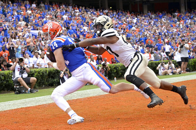 Florida wide receiver Trent Whittemore (14) catches a pass in the end zone for a 9-yard touchdown in front of Vanderbilt safety Brendon Harris (27) during the first half of an NCAA college football game, Saturday, Oct. 9, 2021, in Gainesville, Fla. (AP Photo/Phelan M. Ebenhack)