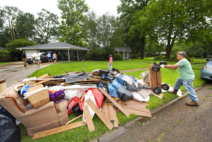 """Homeowner Stephen Punkay, right, dumps a cart-load of wet carpet to add to the debris pile, after the Baker Drive home that he and wife Amy share with their six children got at least six inches of water in Monday night's deluge of rain in the Westminster subdivision, as they clean up with the help of family, neighbors and """"church family"""" from Community Bible Church, on Tuesday, May 18, 2021, in Baton Rouge, La. Heavy rains have swept across southern Louisiana, flooding homes, swamping cars and closing a major interstate. (Travis Spradling/The Advocate via AP)"""