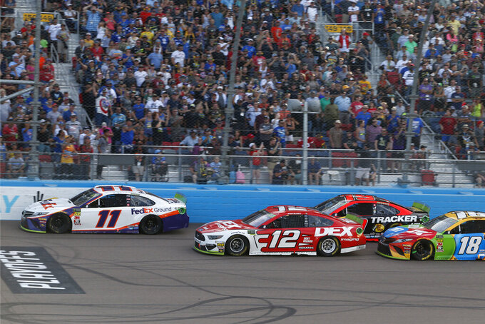 Denny Hamlin (11) leads Ryan Blaney (12), Martin Truex Jr. (19) and Kyle Busch (18) on a restart with three laps to go during a NASCAR Cup Series auto race at ISM Raceway, Sunday, Nov. 10, 2019, in Avondale, Ariz. Hamlin went on to win the race. (AP Photo/Ralph Freso)