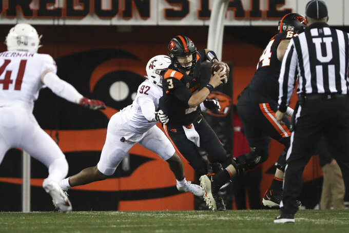 Oregon State quarterback Tristan Gebbia (3) slips a tackle by Washington State linebacker Will Rodgers III (92) during the first half of an NCAA college football game in Corvallis, Ore., Saturday, Nov. 7, 2020. (AP Photo/Amanda Loman)