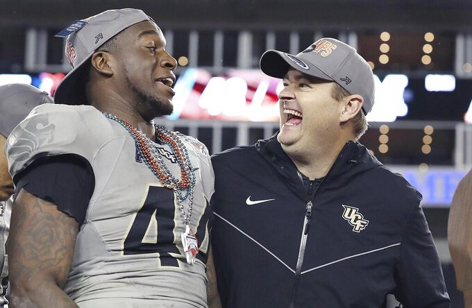 Central Florida linebacker Nate Evans, left, and coach Josh Heupel smile after the team's win over Marshall in the Gasparilla Bowl NCAA college football game Monday, Dec. 23, 2019, in Tampa, Fla. (Stephen M. Dowell/Orlando Sentinel via AP)