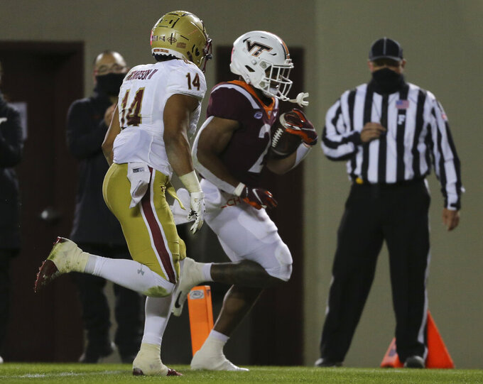 Khalil Herbert, right, of Virginia Tech scores past Sam Johnson III of Boston College in the first half of an NCAA college football game in Blacksburg, Va. Saturday, Oct. 17, 2020. (Matt Gentry/The Roanoke Times via AP, Pool)