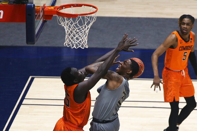 West Virginia forward Gabe Osabuohien (3) shoots while defended by Oklahoma State forward Bernard Kouma (25) during the first half of an NCAA college basketball game Saturday, March 6, 2021, in Morgantown, W.Va. (AP Photo/Kathleen Batten)
