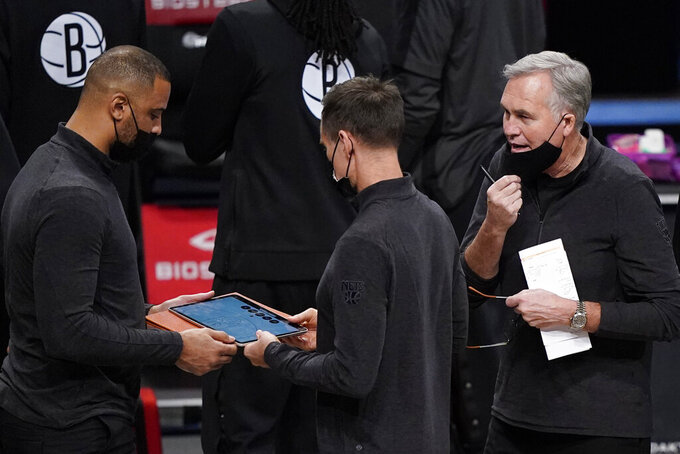 Assistant coach Mike D'Antoni, right, a former New York Knicks head coach, advises Brooklyn Nets head coach Steve Nash, center, during a timeout in the first half of a preseason NBA basketball game against the Washington Wizards, Sunday, Dec. 13, 2020, in New York. (AP Photo/Kathy Willens)