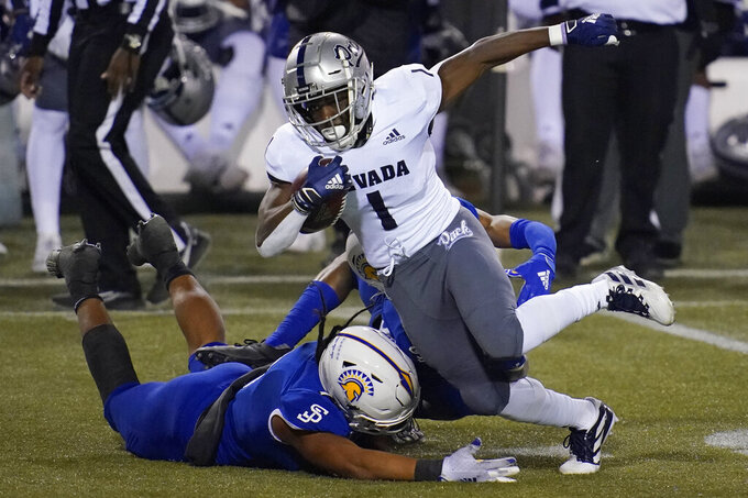 Nevada wide receiver Melquan Stovall (1) tries to avoid San Jose State linebacker Alii Matau, left, during the first half of an NCAA college football game Friday, Dec. 11, 2020, in Las Vegas. (AP Photo/John Locher)