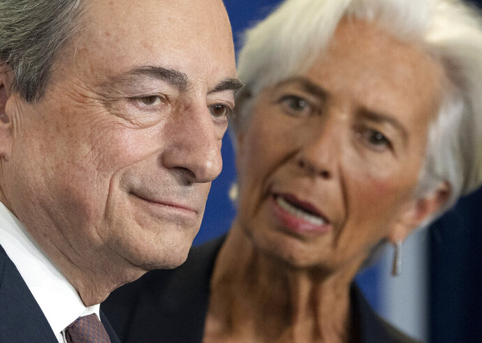 Outgoing European Central Bank President Mario Draghi looks on next to his designated successor Christine Lagarde, at a ceremony celebrating the change at the head of the ECB in Frankfurt, Germany, Monday, Oct. 28, 2019. Draghi leaves as head of the European Central Bank credited with having rescued the eurozone from disaster with a well-timed phrase and bold action to back up his words. (Boris Roessler/Pool Photo via AP)