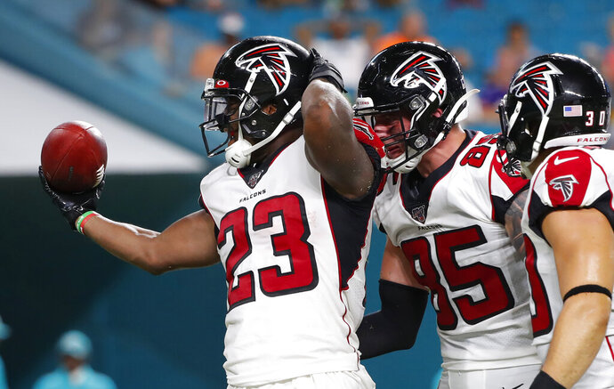 Atlanta Falcons running back Brian Hill (23) celebrates with tight end Eric Saubert (85) after scoring a touchdown during the first half of the team's preseason NFL football game against the Miami Dolphins, Thursday, Aug. 8, 2019, in Miami Gardens, Fla. (AP Photo/Wilfredo Lee)