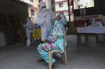 A health worker takes a swab test of a woman during a free medical checkup in Dharavi, one of Asia's biggest slums, in Mumbai, India, Friday, June 26, 2020. India is the fourth hardest-hit country by the pandemic in the world after the U.S., Russia and Brazil. (AP Photo/Rafiq Maqbool)