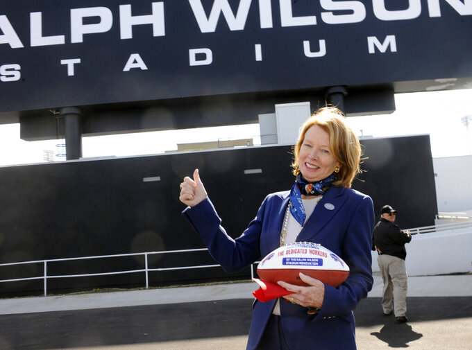 "FILE - In this Sept. 14, 2014, file photo, Mary Wilson, wife of late Buffalo Bills owner Ralph C. Wilson, holds a game ball for stadium construction workers as she gestures to the new renovations to the stadium before an NFL football game against the Miami Dolphins in Orchard Park, N.Y. Wilson is taken aback by how many people have begun noticing the clutch, emblazoned with the Bills' charging buffalo logo, she carries while running errands from her winter home in Florida. ""I'm not trying to advertise or anything, but it's like `Oh, you're a Bills fan. Your team's doing so great,'"" she told The Associated Press by phone. ""I'm so popular now because I'm a Bills fan."" (AP Photo/Gary Wiepert, File)"