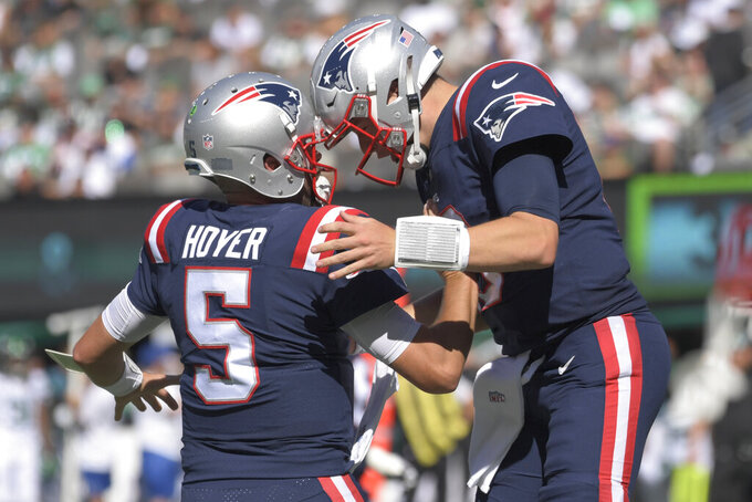 New England Patriots quarterback Mac Jones, right, celebrates a touchdown with back-up quarterback Brian Hoyer during the second half of an NFL football game against the New York Jets, Sunday, Sept. 19, 2021, in East Rutherford, N.J. (AP Photo/Bill Kostroun)