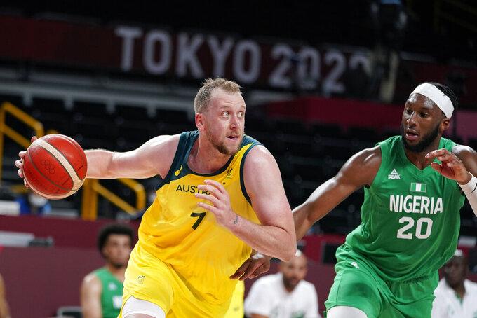 Australia's Joe Ingles drives to the basket past Nigeria's Josh Okogie (20) during a men's basketball preliminary round game at the 2020 Summer Olympics, Sunday, July 25, 2021, in Saitama, Japan. (AP Photo/Charlie Neibergall)