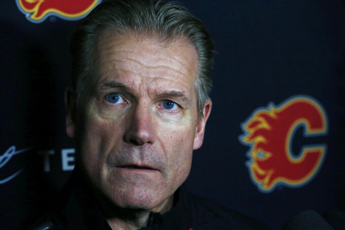 "Calgary Flames associate coach Geoff Ward addresses the media following a NHL hockey practice Tuesday, Nov. 26, 2019, in Buffalo, N.Y. Flames general manager Brad Treliving says coach Bill Peters remains on the staff but wasn't certain whether he'd be behind the bench for the next game. The team and the NHL are both investigating an allegation the Peters directed racial slurs at a player 10 years ago when the two were in the minors. Akim Aliu, a Nigerian-born player, says Peters ""dropped the N bomb several times"" in a dressing room during his rookie year.(AP Photo/Jeffrey T. Barnes)"