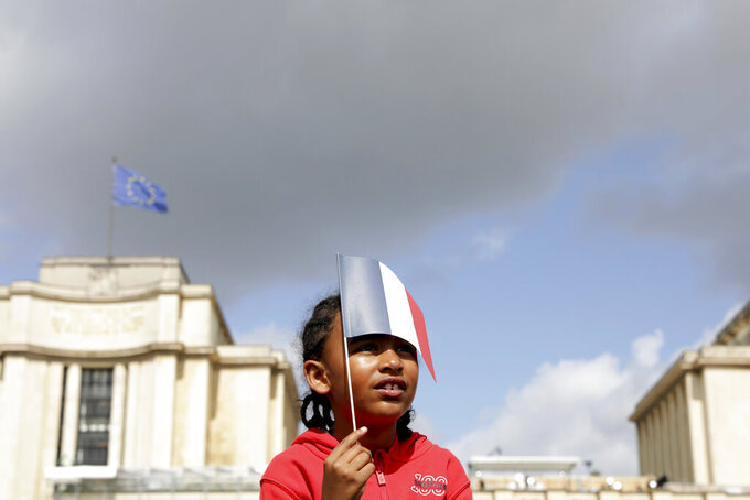 A small girl holds a French flag as she joins others in the Olympics fan zone at the Trocadero in Paris, Sunday, Aug. 8, 2021. A giant flag will be unfurled on the Eiffel Tower in Paris Sunday as part of the handover ceremony of Tokyo 2020 to Paris 2024, as Paris will be the next Summer Games host in 2024. The passing of the hosting baton will be split between the Olympic Stadium in Tokyo and a public party and concert in Paris. (AP Photo/Adrienne Surprenant)
