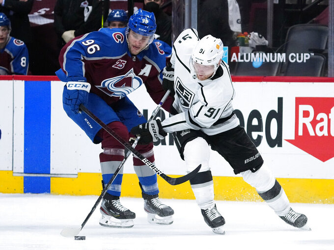 Colorado Avalanche right wing Mikko Rantanen (96) and Los Angeles Kings left wing Carl Grundstrom (91) try to get possession of the puck during the third period of an NHL hockey game Thursday, May 13, 2021, in Denver. (AP Photo/Jack Dempsey)