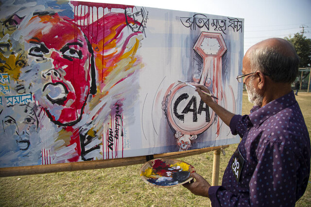 An Indian artist paints on a canvas at an event organized by a students organization to protest against a new citizenship law that opponents say threatens India's secular identity in Gauhati, India, Wednesday, Dec. 25, 2019. Tens of thousands of protesters have taken to India's streets to call for the revocation of the law, which critics say is the latest effort by Narendra Modi's government to marginalize the country's 200 million Muslims.  (AP Photo/Anupam Nath)