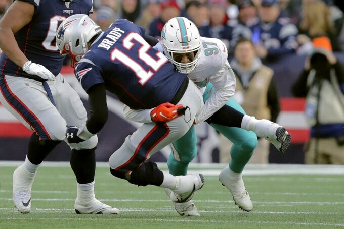Miami Dolphins defensive end Trent Harris, right, sacks New England Patriots quarterback Tom Brady in the second half of an NFL football game, Sunday, Dec. 29, 2019, in Foxborough, Mass. (AP Photo/Charles Krupa)
