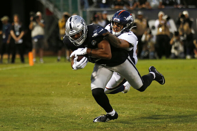 Oakland Raiders wide receiver Tyrell Williams scores a touchdown as Denver Broncos free safety Justin Simmons looks on during the first half of an NFL football game Monday, Sept. 9, 2019, in Oakland, Calif. (AP Photo/D. Ross Cameron)