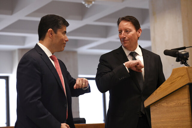 Florida House speaker Jose Oliva, R-Miami Lakes, left, and Senate President Bill Galvano, R-Bradenton bump elbow ]s during a press conference on the Fourth Floor Rotunda at the Capitol, Thursday, March 19, 2020 in Tallahassee, Fla. (AP Photo/Aileen Perilla)
