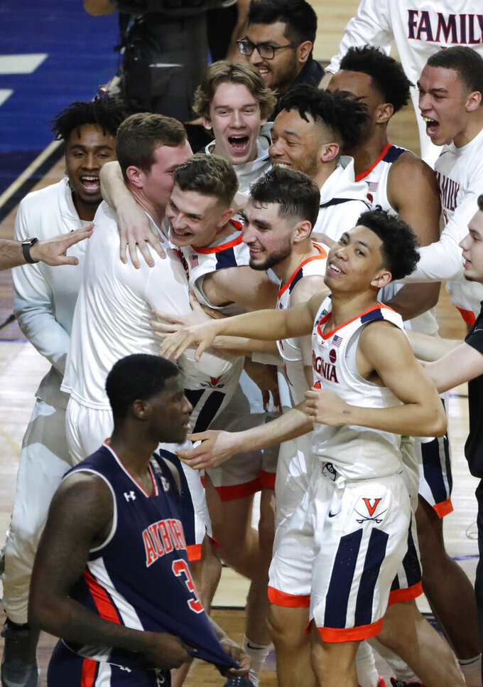 Virginia players celebrate in front of Auburn forward Danjel Purifoy (3) after a semifinal round game in the Final Four NCAA college basketball tournament, Saturday, April 6, 2019, in Minneapolis. (AP Photo/Matt York)