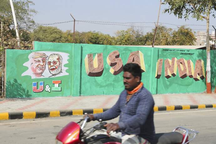 A man rides past a wall painted with portraits of U.S. President Donald Trump and Indian Prime Minister Narendra Modi ahead of Trump's visit, in Ahmadabad, India, Tuesday, Feb. 18, 2020. Trump is scheduled to visit the city during his Feb. 24-25 India trip. (AP Photo/Ajit Solanki)