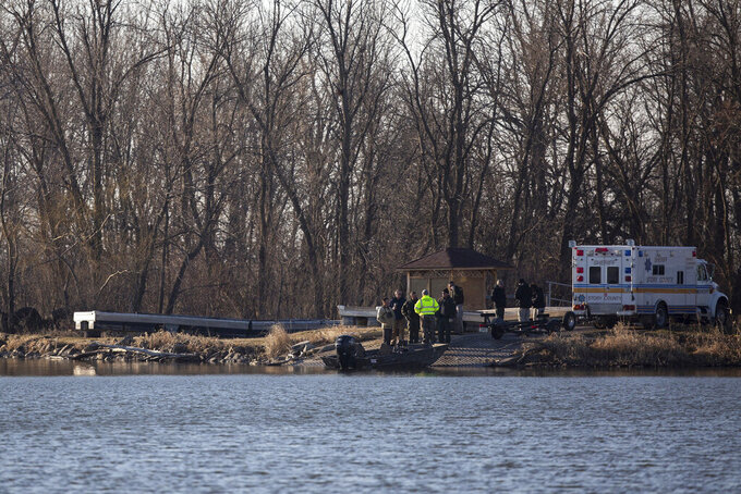 Law enforcement gather near a boat ramp on Little Wall Lake as they resume the search for a missing Iowa State University Crew Club member on Monday, March 29, 2021, in Hamilton County. The ISU student has been missing since the rescue of three other students and the death of one on the lake Sunday. (Kelsey Kremer/The Des Moines Register via AP)
