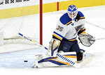 St. Louis Blues goaltender Ville Husso deflects the puck during the first period of the team's NHL hockey game against the Vegas Golden Knights on Saturday, May 8, 2021, in Las Vegas. (AP Photo/David Becker)