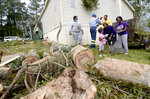Members of the Veal family clean up on Saturday, Oct. 10, 2020, after Hurricane Delta dropped a tree on their house in Gloster, Miss. (Matt Williamson/The Enterprise-Journal via AP)