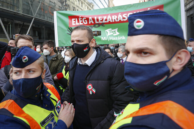 Laszlo Toroczkai, center, head of the Our Homeland Movement is flanked by police officers during a protest in Budapest, Hungary, Monday, March 15, 2021. Hungarians gathered on the country's national day to protest against the current lockdown measures after new restrictive measures were introduced by the Hungarian government last week aiming to slow a record-breaking wave of COVID-19 hospitalizations and deaths. (AP Photo/Laszlo Balogh)