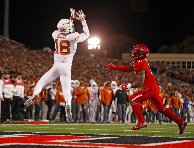 Texas' Davante Davis (18) intercepts a pass in the end zone during the first half of an NCAA college football game against Texas Tech, Saturday, Nov. 10, 2018, in Lubbock, Texas. (AP Photo/Brad Tollefson)