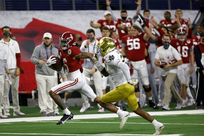 The Alabama sideline erupts in celebration as wide receiver DeVonta Smith (6) sprints to the end zone for a touchdown as Notre Dame safety Shaun Crawford (20) gives chase in the first half of the Rose Bowl NCAA college football game in Arlington, Texas, Friday, Jan. 1, 2021. (AP Photo/Ron Jenkins)