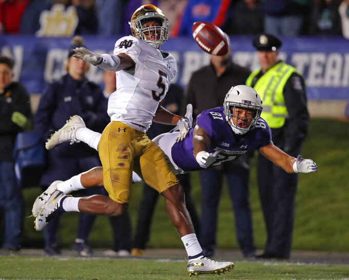 Northwestern's Ramaud Chiaokhiao-Bowman, right, dives for the ball but cannot make the catch as he is guarded by Notre Dame's Troy Pride Jr. during the first half of an NCAA college football game Saturday, Nov. 3, 2018, in Evanston, Ill. (AP Photo/Jim Young)